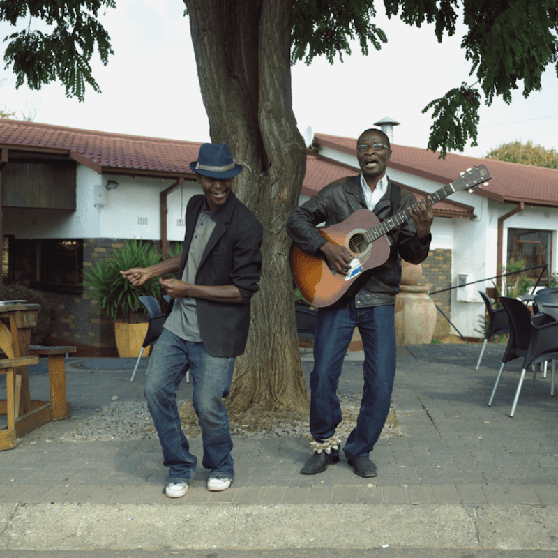 """In front of Mandela House at a local restaurant two musicians play a little tune, Soweto, Johannesgurg, South Africa."""